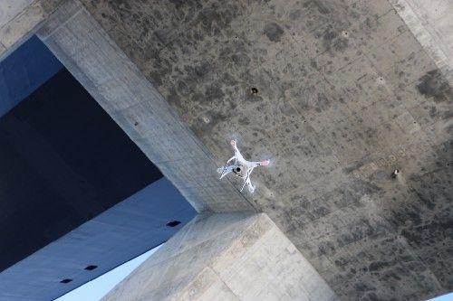 photograph of a drone flying beneath a concrete bridge
