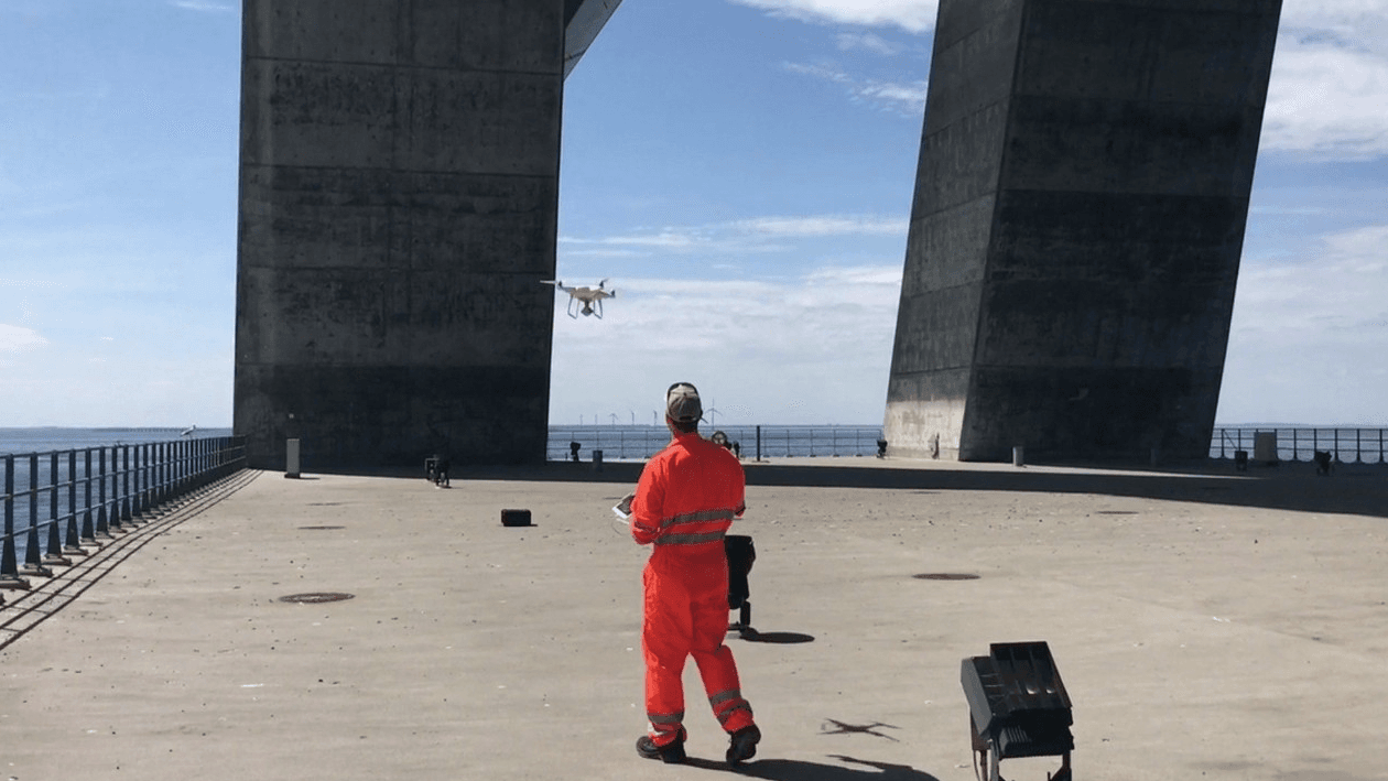 Photograph of a man in an orange work suit operating a drone under the pillars of a bridge