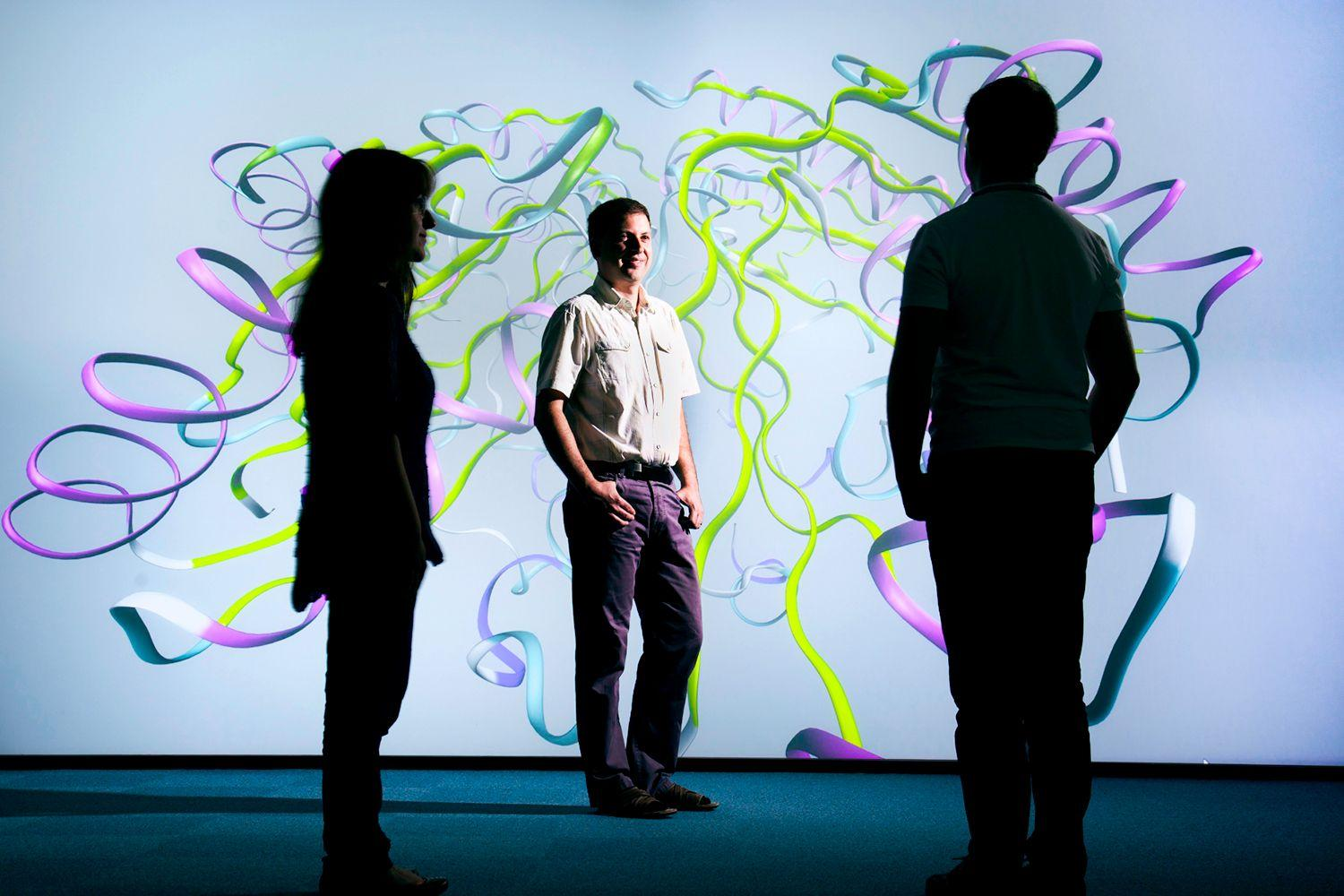 Photograph of the visualisation suite at the Hartree National Centre for Digital Innovation with three people against a backdrop of full screen wall with a ribbon diagram of a molecular structure